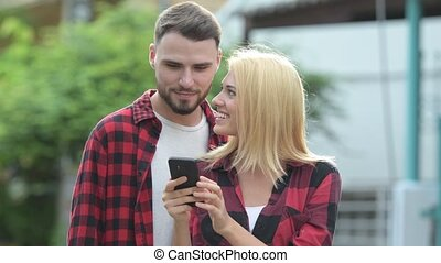 Young happy couple using phone together in the streets...