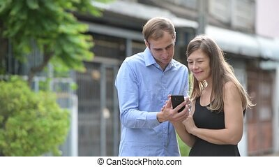 Young happy couple using phone together outdoors