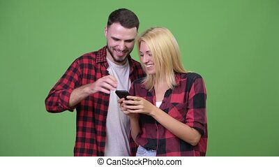 Young happy couple using phone together - Studio shot of...