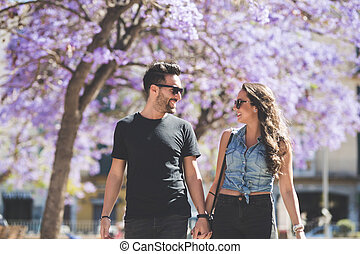 Young happy couple walking together holding hands