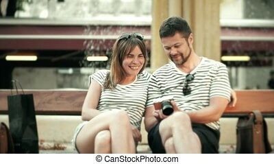 Young happy couple watching photos in the compact camera on...