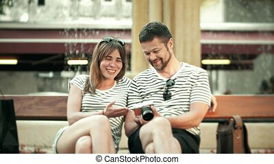 Young happy couple watching photos in the compact camera on their vacation