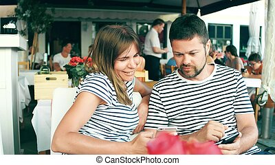 Young happy couple watching photos on the smart phone in a cafe