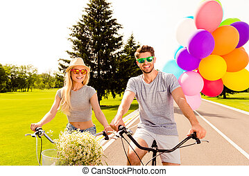 Young happy couple with balloons on a bike ride in the park