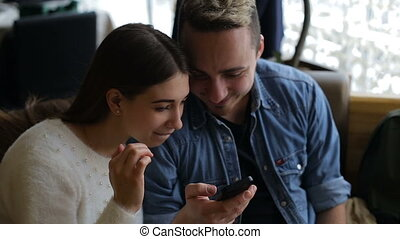 Young happy couple with smartphone in cafe