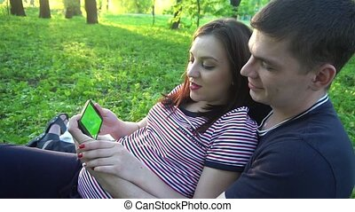 Young happy couple with smartphone, outdoors.Park....