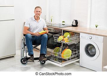 Disabled Man On Wheelchair In Kitchen