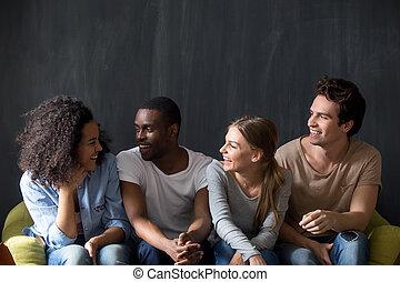 Young happy diverse friends listening to biracial smiling girls joke.