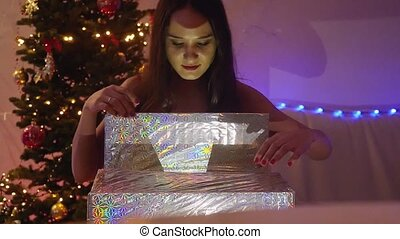 Young happy emotional woman opening the magical Christmas present in slowmotion. Girl sits next to Xmas tree at decorated home. 1920x1080