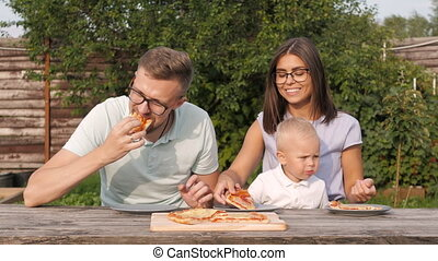 Young Happy Family Having Picnic In The Garden. Mom, Dad And Son Eating Pizza Outdoors