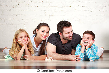 Young happy family parents and two children at home studio