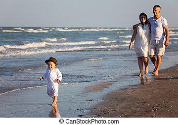 Young happy family walking along the seashore
