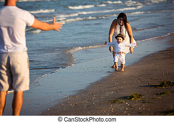 Young happy family walking on the beach
