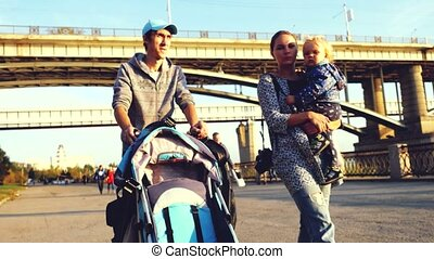 Young happy family with a little son and pram walking...