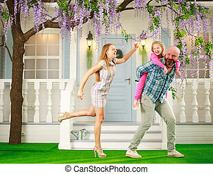 Young happy family with child daughter play fun at home in yard in spring flowering garden