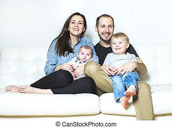 Young happy family with two children at home