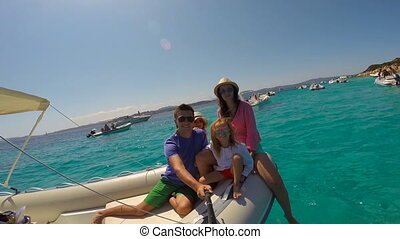 Young happy family with two little girls on a big boat during sammer vacation in Italy