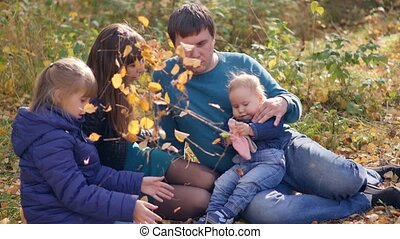 Young happy family with young children resting in the autumn park on a sunny day