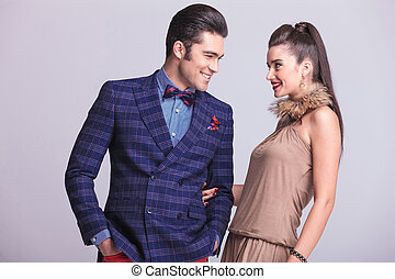Young happy fashion couple looking at each other