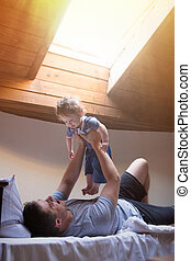 Young happy father and child play in a bed