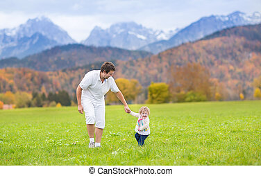 Young happy father playing with his baby daughter in a beautiful