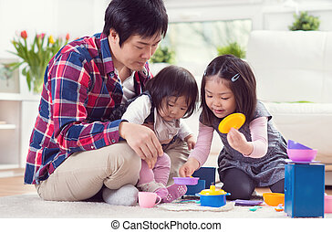 Young happy father playing with pretty daughters and having fun at home
