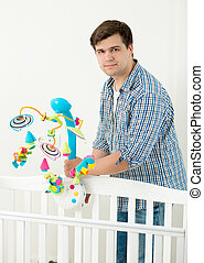 Young happy father showing new toy carousel in cot to his baby son