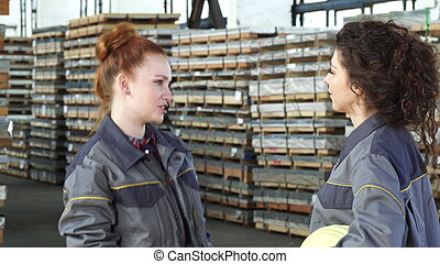Young happy female factory workers high fiving at the warehouse