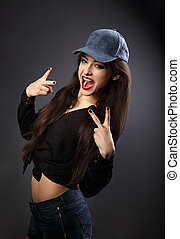 Young happy female model in blue hat showing rock gesture in...
