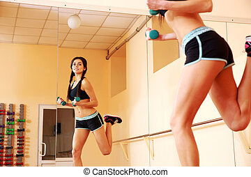 Young happy fit woman doing exercises with dumbells and looking on her reflection in mirror at gym