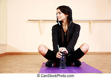 Young happy fit woman sitting on yoga mat and looking away...