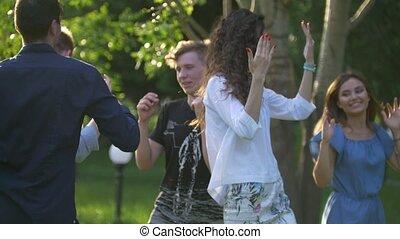 Young happy friends having fun dancing in summer park