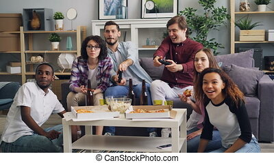 Young happy friends playing video games talking eating having fun at home party