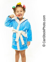 Young happy girl brush her teeth in blue dressing gown with...