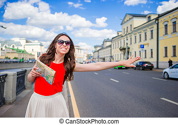 Young happy girl catch a taxi with city map in hands. Portrait of a beautiful happy woman standing on the street smiling and catching a taxi