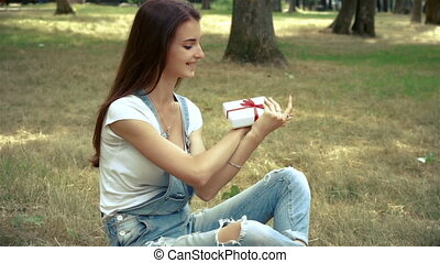 young happy girl holds and treats gift sitting outside