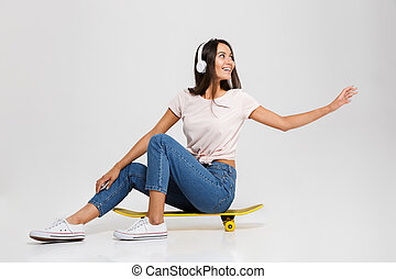 Young happy girl in white headphone with outstretched hand,...