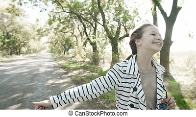 Young happy girl is catching a car on the road. A little...