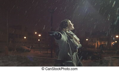 Young happy girl is enjoying the falling snow holding up his hands.