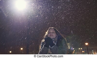 Young happy girl is enjoying the falling snow, raising his hands. Cold. Winter.