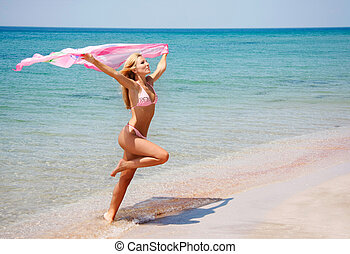 young happy girl jumping on beach