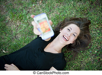 Young happy girl laughing at phone