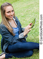 Young happy girl looking at the camera while touching her tablet pc in a parkland