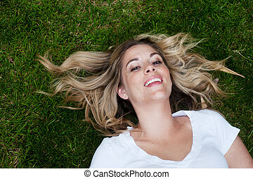 Young happy girl lying in the grass