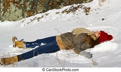 Young happy girl lying in the snow