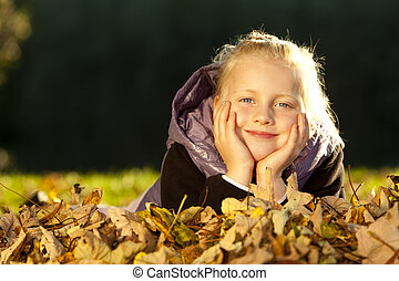 Young happy girl lying on floor in autumn leaves
