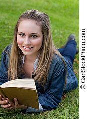 Young happy girl lying on the grass in the countryside while reading a book