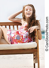 young happy girl on beach sofa over white