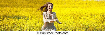 young happy girl running in yellow flower field