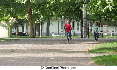 Young happy girl running it park with her sister together. Slow motion